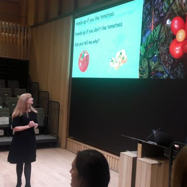 nainen pitää esitelmää luentosalissa ja näyttää tomaattien kuvaa
