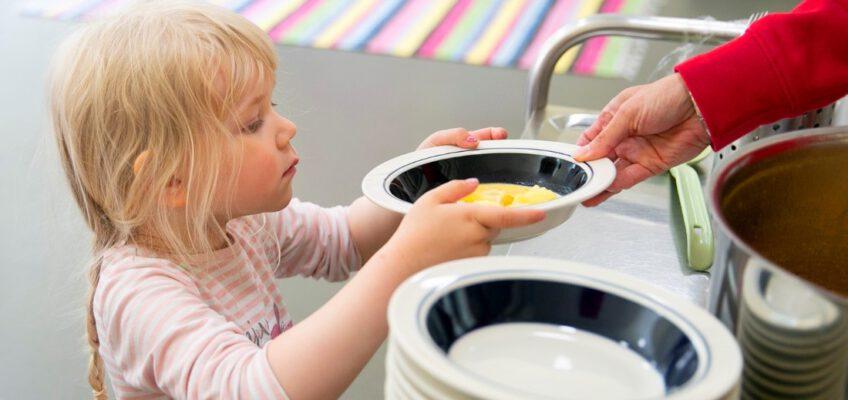 pieni tyttö ottaa keittolautasen